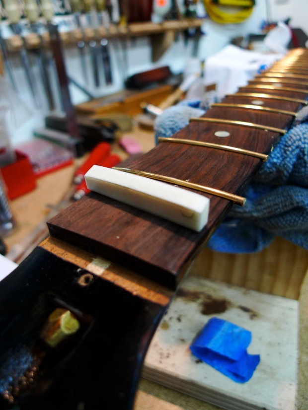 The unfinished nut blank, and the freshly fretted neck.  More to come, after the glue is set!