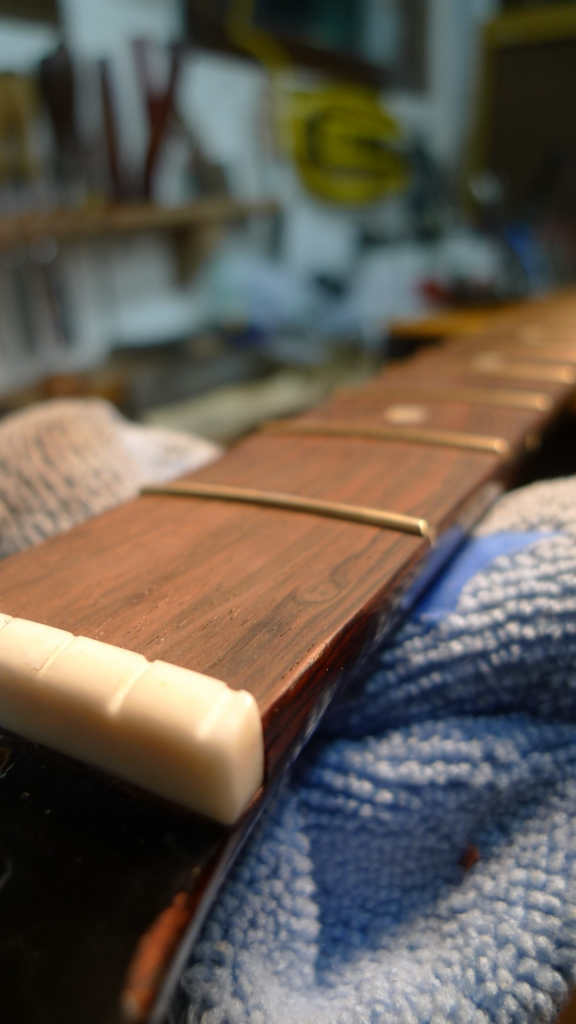 The board is dressed, the new bone nut made, and frets hammered, glued, and dressed.