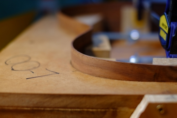 Claro Walnut ribs are bent by hand over a hot iron, and carefully fit to the MDF body mould.