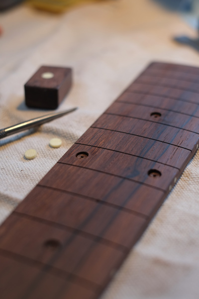 "1/4"" ivoroid dots are cut with a plug cutter and inlaid into the fingerboard"