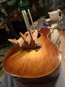 The bridge gets glued on with hot hide glue, using cauls on both sides of the bridge/bridge plate.  I made the bridge plate caul while the top was off the guitar, so the bridge will get some nice full-clamping action.